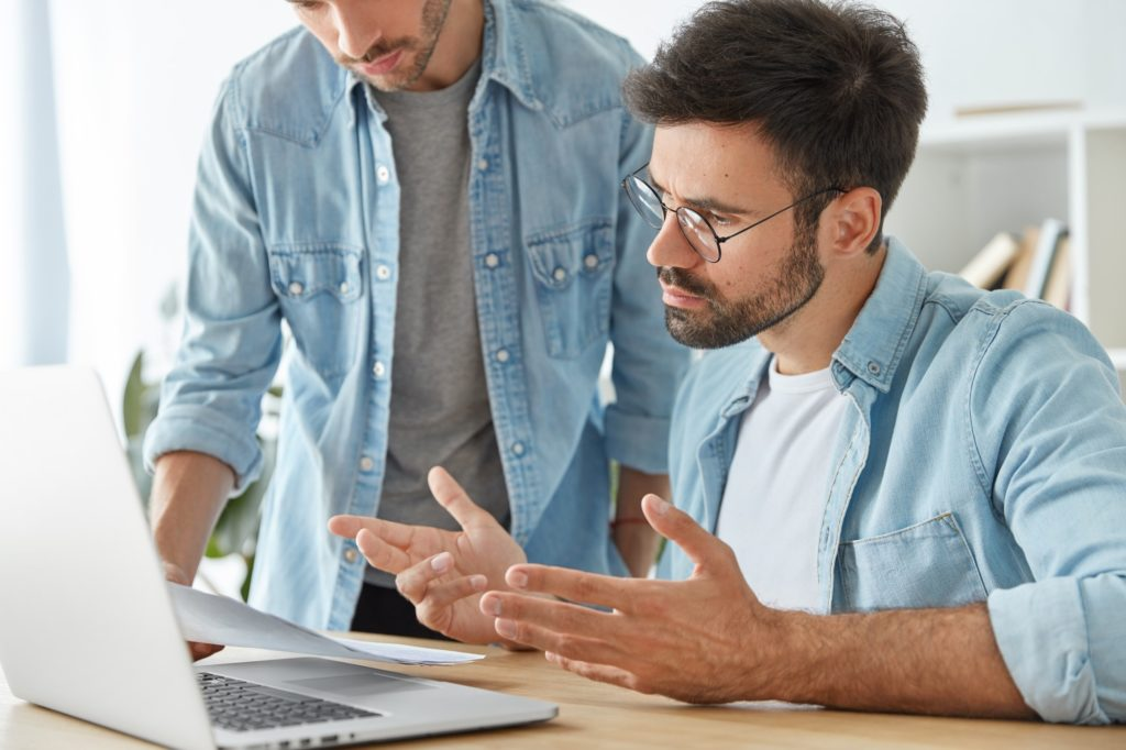 Serious bearded Caucasian male employee consults with intelligent colleague, looks attentively into