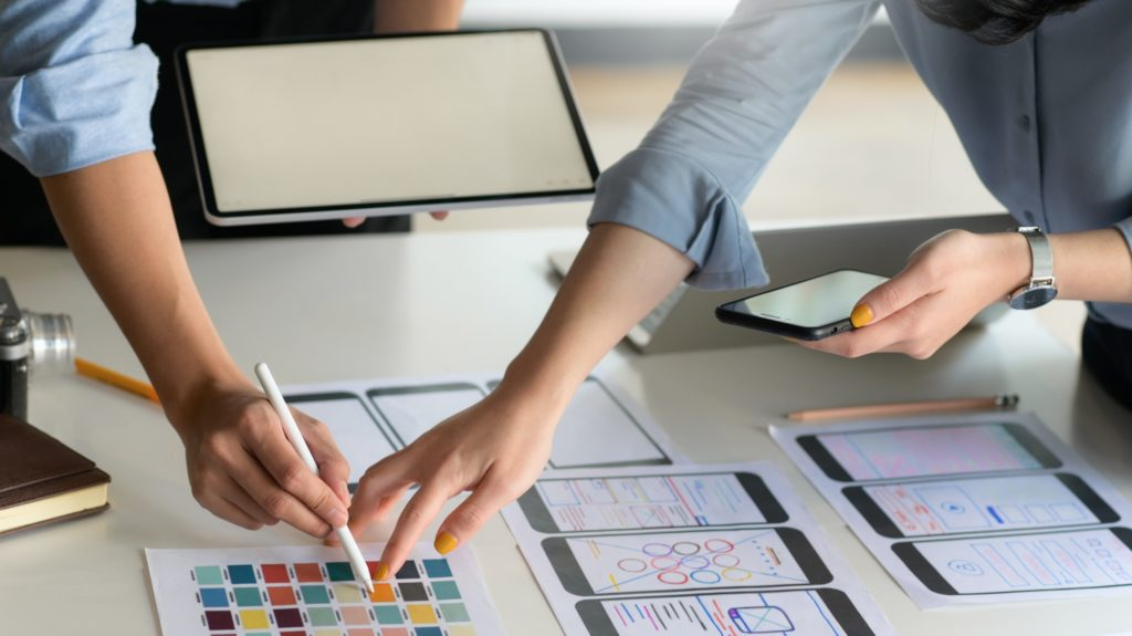 UX,UI professional team with smartphone and tablet is designing new projects.